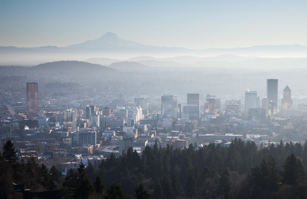 A view to the east on a hazy morning. Mt. Hood rises above the city skyline of Portland. The sun was reflecting off the buildings, giving a sort of back-glow.